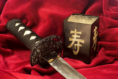Katana. Small japanese sword and candlestick on a red fabric stock photo