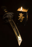 Katana. Small japanese sword and candlestick isolated on black background stock images