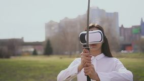 Katana asiático del control de la persona orgulloso mientras que juega al juego del vr en vidrios futuros especiales almacen de metraje de vídeo