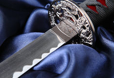 Katana on blue satin. Close-up of Japanese katana sword on blue satin background Stock Image