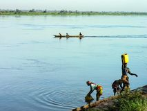 Katanga, DRC: Women fetching water from river Congo royalty free stock images