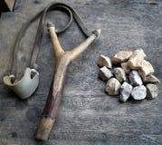 Katapult met stenen op houten achtergrond stock afbeelding