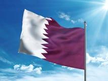 Katar fahnenschwenkend im blauen Himmel Lizenzfreies Stockfoto