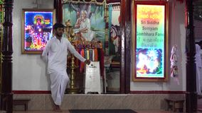 Kataragama, Σρι Λάνκα - 2019-03-29 - στάσεις ατόμων μπροστά από τα φανταχτερά φθορισμού σημάδια που γιορτάζουν τους ινδούς Θεούς φιλμ μικρού μήκους