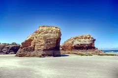 Kathedralen setzen in der Ebbe mit den Felsen auf den Strand, die durch die Aktion des Meeres erosioned sind stockbild