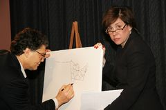 Al Franken and Katherine Lanpher. Katherine Lanpher watches as co-host, comedian Al Franken, draws free-hand a detailed state demarcated map of the United during Royalty Free Stock Photos