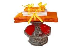 Kathin-Gewebe, Kathin-Zeremonie, Kleider des buddhistischen Mönchs in einem geschnitzten Traditionsperlenbehälter mit Beschneid stockbild