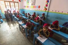 KATHMANDU, NEPAL - allievi sconosciuti nella classe inglese alla scuola primaria Soltanto 50% dei bambini nel Nepal può raggiunge Fotografia Stock