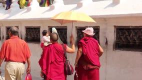 Kathmandu, Nepal - CIRCA 2013: Buddhist monks walk by prayer wheels near a stupa. Kathmandu, Nepal - CIRCA 2013: Buddhist monks and Nepali people walk by prayer stock footage