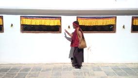 Buddhist Monk spins prayers wheels at Boudhanath Stupa in Kathmandu, Nepal. 3D sound. stock video