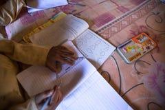 KATHMANDU, NEPAL - crianças desconhecidas que fazem trabalhos de casa na escola de Jagadguru imagem de stock royalty free