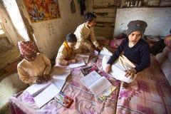 KATHMANDU, NEPAL - crianças que fazem trabalhos de casa na escola de Jagadguru imagem de stock royalty free