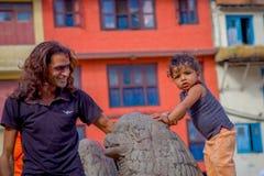 KATHMANDU, NEPAL 15 DE OUTUBRO DE 2017: Feche acima de homem não identificado com seu daugher fora do quadrado de Durbar, Kathman Fotografia de Stock