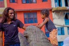 KATHMANDU, NEPAL 15 DE OUTUBRO DE 2017: Feche acima de homem não identificado com seu daugher fora do quadrado de Durbar, Kathman Imagens de Stock
