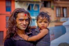 KATHMANDU, NEPAL 15 DE OUTUBRO DE 2017: Feche acima de homem não identificado que realiza em seus braços seu daugher fora de Durb Imagens de Stock