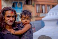 KATHMANDU, NEPAL 15 DE OUTUBRO DE 2017: Feche acima de homem não identificado que realiza em seus braços seu daugher fora de Durb Foto de Stock