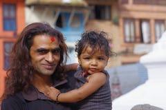 KATHMANDU, NEPAL 15 DE OUTUBRO DE 2017: Feche acima de homem não identificado que realiza em seus braços seu daugher fora de Durb Imagem de Stock