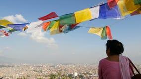 Kathmandu, Nepal - 12 de outubro de 2018 Mulher étnica que olha a arquitetura da cidade Ideia de acenar bandeiras coloridos da or video estoque