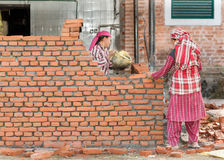 KATHMANDU, NEPAL - DECEMBER 17, 2012: Nepali construction mason women workers bricklayer making a brickwork with trowel and cement Royalty Free Stock Images