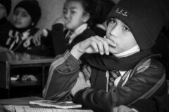 A Young Boy Sitting in School Looking Bored