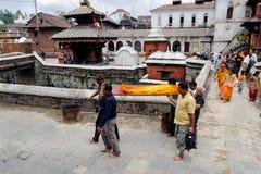 KATHMANDU, NEPAL - 2. JULI 2013: Lokale Leute des Nepali, die eine Leiche zur Verbrennungszeremonie entlang dem heiligen Bagmati- Stockbild