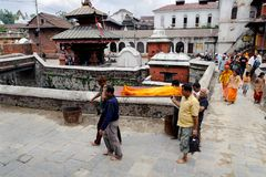 KATHMANDU, NEPAL - JULY 2, 2013: Nepali local people carrying a dead body to the cremation ceremony along the holy Bagmati River i Stock Image