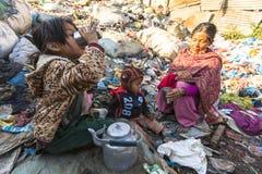 KATHMANDU, NEPAL - Kind und seine Eltern während des Mittagessens im Bruch zwischen dem Arbeiten an Dump Stockbilder