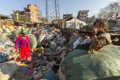 KATHMANDU, NEPAL - Kind und seine Eltern während des Mittagessens im Bruch zwischen dem Arbeiten an Dump Stockbild