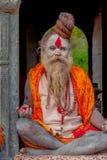 KATHMANDU NEPAL, MARZEC, - 22, 2017: Zamyka up joga Shaiva sadhu obsiadanie w Pashupatinath świątyni Kathmandu z jego Zdjęcie Stock