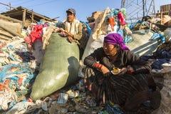 KATHMANDU, NEPAL - nicht identifizierte lokale arme Leute während des Mittagessens im Bruch zwischen dem Arbeiten an Dump Stockfoto
