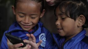Kathmandu, Nepal - 27 November 2019: Happy little Indian Nepali children play in a smartphone and a young caucasian girl