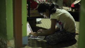Kathmandu, Nepal - 27 November 2019: An energetic Indian Nepali teenage girl works on a laptop sitting right on the