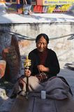 KATHMANDU, NEPAL - NOVEMBER 26, 2011: Old Tibetan buddhist lady prayer rosary at Baudhanath Temple. As of 1979, Boudhanath is a UN Royalty Free Stock Photo