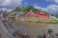 KATHMANDU, NEPAL OCTOBER 15, 2017: Beautiful landscape with some buildings where the Religious burning ritual at. Pashupatina temple happen, with a dirty river stock photography