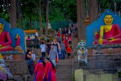 KATHMANDU, NEPAL OCTOBER 15, 2017: Crowd of peoplewalking close to a stoned statue and prayer flags in Swayambhu Royalty Free Stock Images