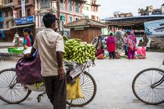 Man sells bananas on a bike on a street market. Kathmandu, Nepal, - October 05, 2017: Man sells bananas on a bike on a street market Stock Image