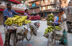 Man sells bananas on a bike on a street market. Kathmandu, Nepal, - October 05, 2017: Man sells bananas on a bike on a street market Royalty Free Stock Images
