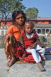 Kathmandu, Nepal, October, 27, 2012, Nepali  Scene: the poor woman with a child begging in ancient Pashupatinath complex on the ba Royalty Free Stock Images