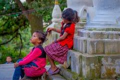 KATHMANDU, NEPAL AM 15. OKTOBER 2017: Nicht identifizierte Kinder, die am Freien nah an Swayambhu, ein altes religiöses sitzen Lizenzfreie Stockfotos