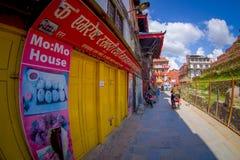 KATHMANDU, NEPAL AM 15. OKTOBER 2017: Nicht identifizierte Leute, die ein Motorrad in einer kleinen entsteinten Straße im Kathman Stockfotografie