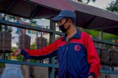 KATHMANDU, NEPAL AM 15. OKTOBER 2017: Nicht identifizierter Mann, einige Gebetsräder an Swayambhu-Tempel alias berührend Lizenzfreie Stockfotografie