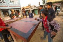 KATHMANDU, NEPAL - os adolescentes das famílias pobres jogam no tênis de mesa nos precários fotografia de stock