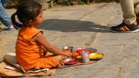 KATHMANDU, NEPAL - 8 OTTOBRE 2018 vista laterale di piccola ragazza etnica che vende i vari attributi religiosi, sedentesi sulla  stock footage