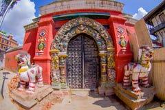 KATHMANDU, NEPAL PAŹDZIERNIK 15, 2017: Zamyka up dwa drylującego opiekunu wchodzić do świątynia z niektóre rzeźbiącą strukturą, Zdjęcie Stock