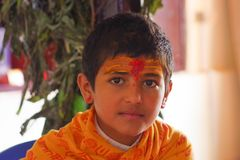 KATHMANDU, NEPAL - SEPTEMBER 04, 2017: Portrait of young Nepalese boy wearing typical clothes and some orange and red Stock Photo