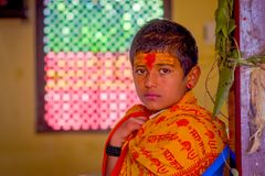 KATHMANDU, NEPAL - SEPTEMBER 04, 2017: Portrait of young Nepalese boy wearing typical clothes and some orange and red. Color in his forehead, in Nepal Stock Image