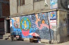 Kathmandu, Nepal, September, 27, 2013, Street trading at the wall with graffiti on Buddhist themes in Kathmandu Stock Photos