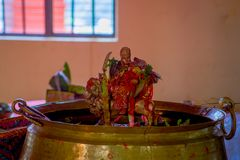 KATHMANDU, NEPAL - SEPTEMBER 04, 2017: Unidentified people inside of a building giving an oblation food and flowers to. Their goods, golden figures and praying Stock Photo