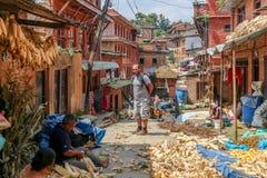 Kathmandu, Nepal - 22 settembre 2016: Turista che guarda la gente nepalese preparare i semi per la vendita sulla via nel Nepal Fotografia Stock