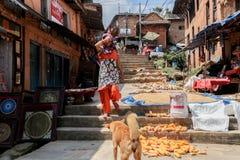 Kathmandu, Nepal - 22 settembre 2016: Vestito nepalese dalla donna che cammina giù i punti sulla via con i negozi nel Nepal Fotografia Stock